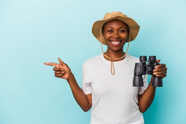 Jonge afro-amerikaanse vrouw met verrekijker geïsoleerd op blauwe achtergrond glimlachend en opzij wijzend, iets tonend op lege ruimte.