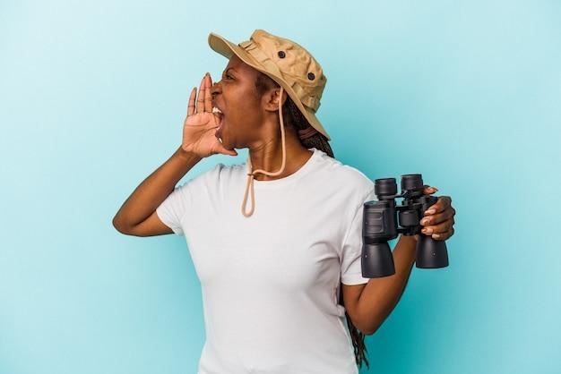 Jonge afro-amerikaanse vrouw met verrekijker geïsoleerd op blauwe achtergrond schreeuwen en houden palm in de buurt van geopende mond.