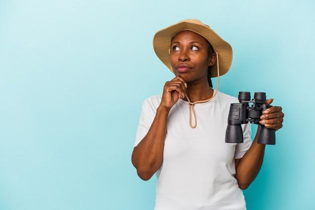 Jonge afro-amerikaanse vrouw met verrekijker geïsoleerd op blauwe achtergrond zijwaarts kijkend met twijfelachtige en sceptische uitdrukking.