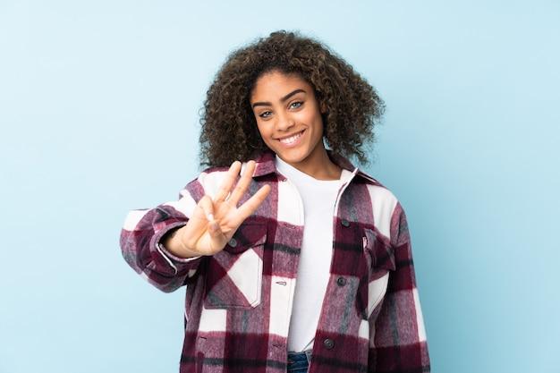 Jonge afro-amerikaanse vrouw op blauwe muur gelukkig en tellen drie met vingers