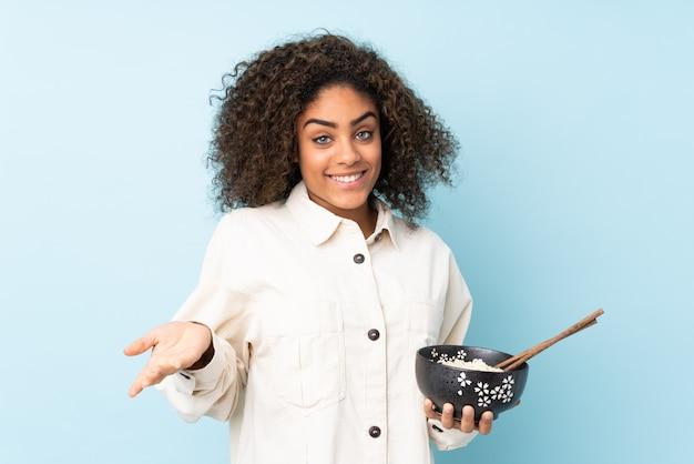 Jonge afro-amerikaanse vrouw op blauwe muur met geschokte gelaatsuitdrukking terwijl een kom noedels met stokjes
