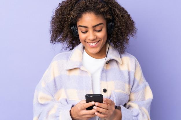 Jonge afro-amerikaanse vrouw op paarse muur luisteren muziek en op zoek naar mobiel