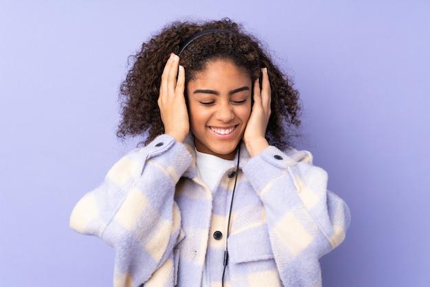 Jonge afro-amerikaanse vrouw op paarse muur luisteren muziek