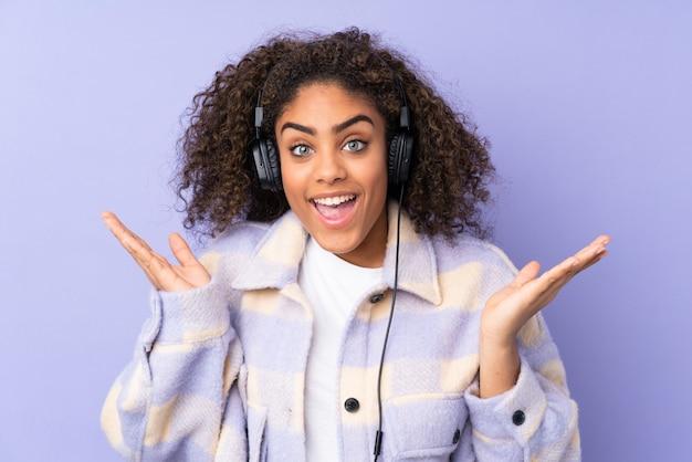 Jonge afro-amerikaanse vrouw op paarse muur verrast en muziek luisteren
