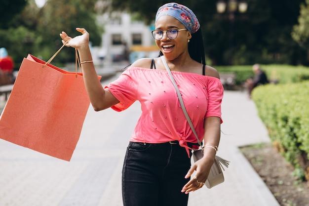 Jonge afro-amerikaanse vrouw op straat met boodschappentassen
