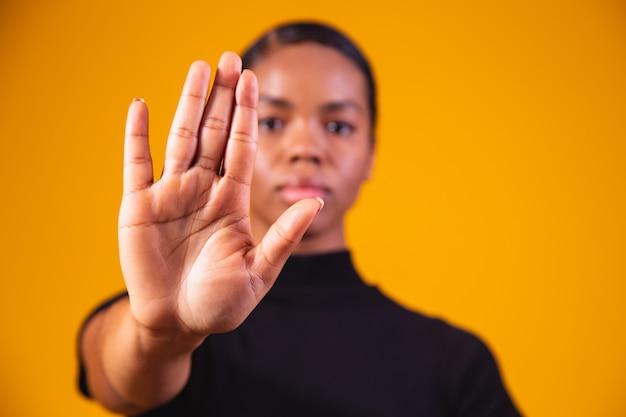 Jonge afro-amerikaanse vrouw toonde hand op teken voor hen om te stoppen met raciale vooroordelen.