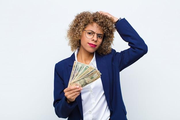 Jonge afro-amerikaanse vrouw verbaasd en verward gevoel, hoofd krabben en op zoek naar de kant met eurobankbiljetten