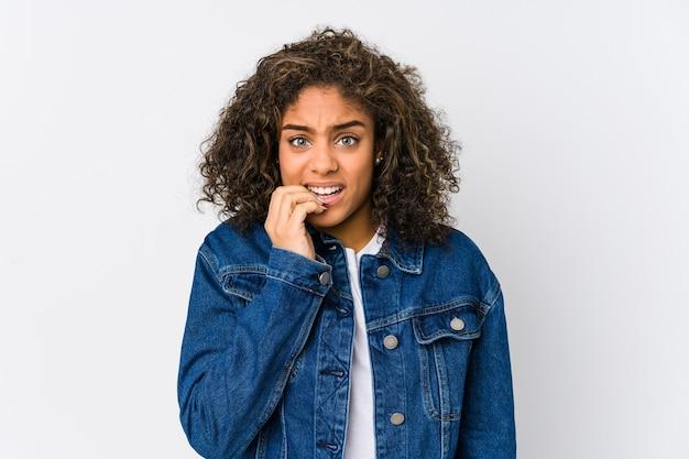 Jonge afro-amerikaanse vrouw vingernagels bijten, nerveus en erg angstig.