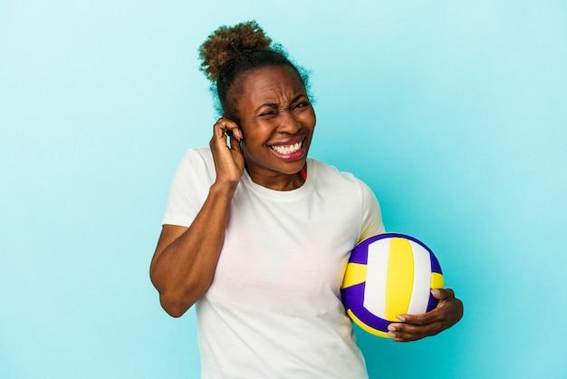 Jonge afro-amerikaanse vrouw volleyballen geïsoleerd op blauwe achtergrond die betrekking hebben op oren met handen.