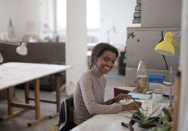 Jonge afro-amerikaanse vrouw werkt vanuit huis vanwege de wereldwijde pandemie
