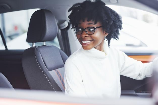 Jonge afro-amerikaanse vrouw zit binnenkant van nieuwe moderne auto.