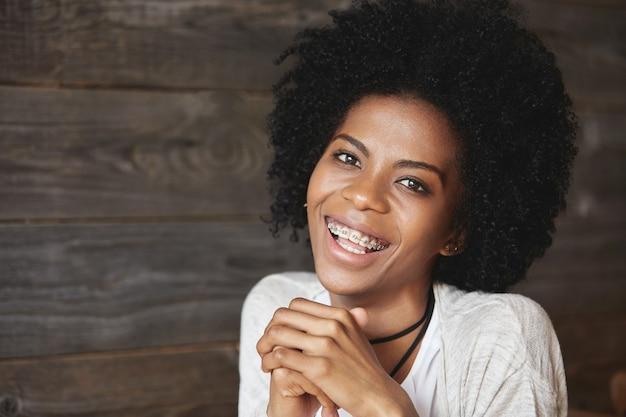 Jonge afro-amerikaanse vrouw zitten in café