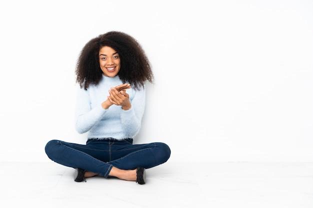 Jonge afro-amerikaanse vrouw zittend op de vloer applaudisseren na presentatie in een conferentie