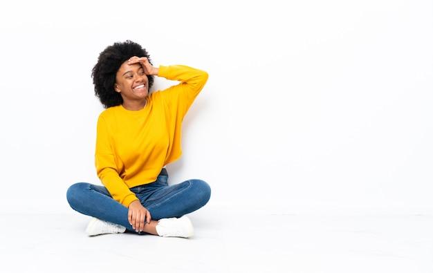 Jonge afro-amerikaanse vrouw zittend op de vloer heeft iets gerealiseerd en de oplossing voornemens