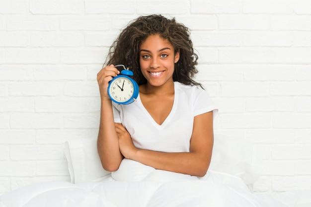 Jonge afro-amerikaanse vrouw zittend op het bed met een wekker glimlachend zelfverzekerd met gekruiste armen.