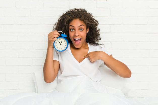Jonge afro-amerikaanse vrouw zittend op het bed met een wekker verrast wijzend op zichzelf, breed lachend.