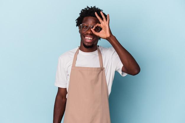 Jonge afro-amerikaanse winkelbediende geïsoleerd op blauwe achtergrond opgewonden houden ok gebaar in de gaten.