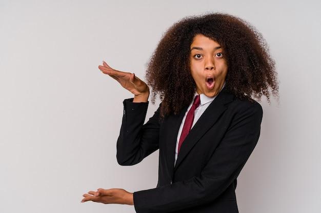 Jonge afro-amerikaanse zaken vrouw, gekleed in een pak geïsoleerd op wit geschokt en verbaasd met een kopie ruimte tussen handen.