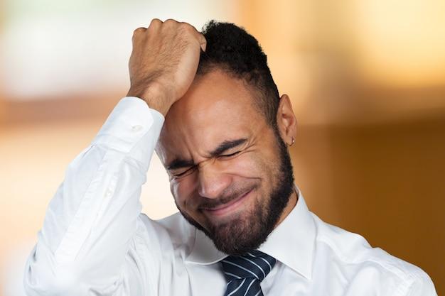Jonge afro-amerikaanse zakenman die aan hoofdpijn lijdt na een harde werkdag