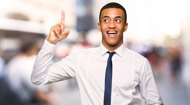 Jonge afro amerikaanse zakenman die de oplossing probeert te realiseren terwijl het opheffen van een vinger in de stad