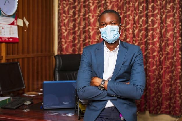 Jonge afro-amerikaanse zakenman die een beschermend masker draagt in zijn kantoor