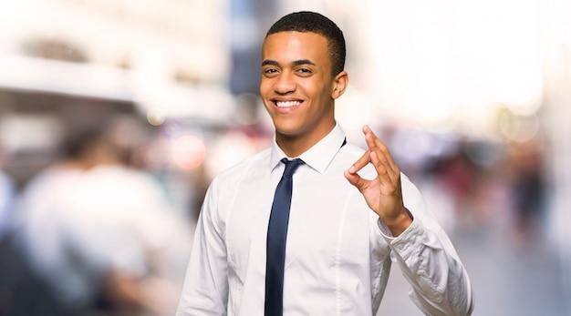 Jonge afro amerikaanse zakenman die een ok teken met vingers in de stad toont