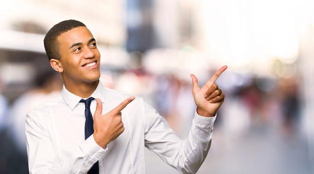 Jonge afro amerikaanse zakenman die met de wijsvinger richt en omhoog in de stad kijkt
