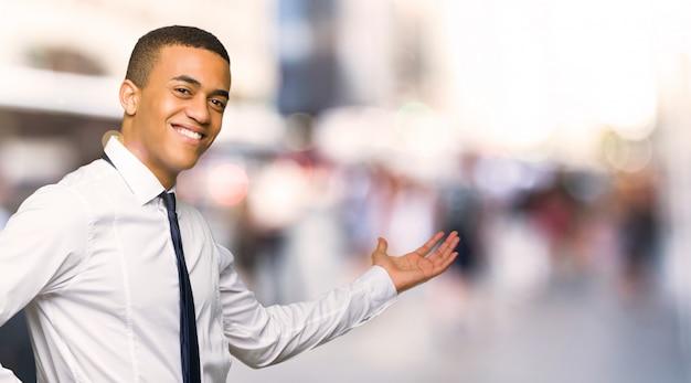 Jonge afro amerikaanse zakenman die terug en een product in de stad voorstellen voorstellen