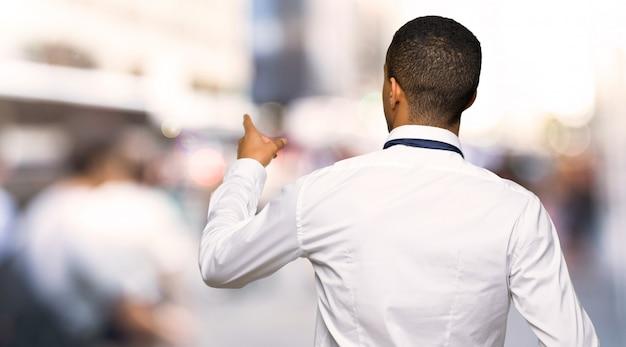 Jonge afro amerikaanse zakenman die terug met de wijsvinger in de stad richten