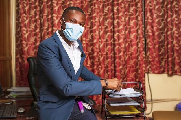 Jonge afro-amerikaanse zakenman draagt een beschermend masker in zijn kantoor