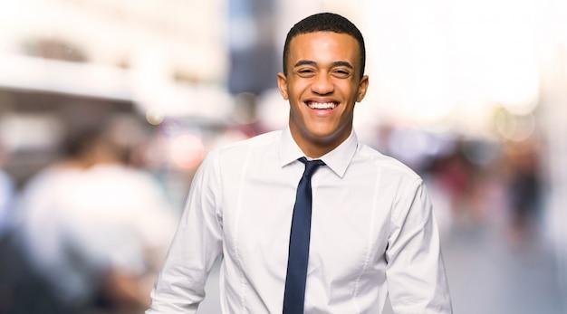Jonge afro amerikaanse zakenman gelukkig en glimlachend in de stad