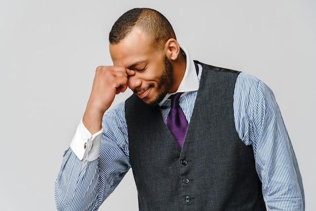 Jonge afro-amerikaanse zakenman hoofd aan te raken vanwege hoofdpijn en stress.