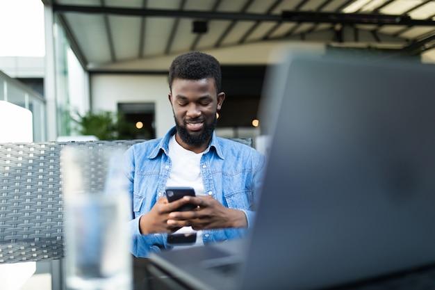 Jonge afro-amerikaanse zakenman met bril en laptop zitten in café-bar en mobiele telefoon gebruiken.