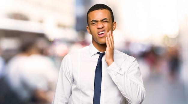 Jonge afro amerikaanse zakenman met tandpijn in de stad