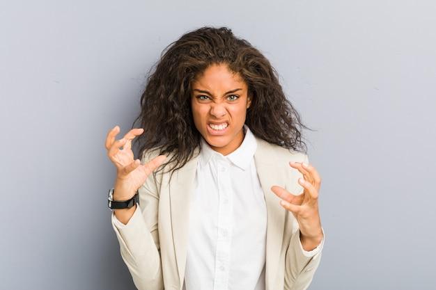Jonge afro-amerikaanse zakenvrouw boos schreeuwen met gespannen handen
