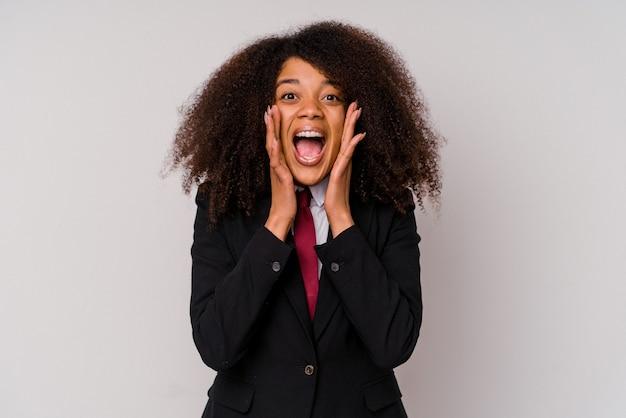 Jonge afro-amerikaanse zakenvrouw die een pak draagt dat op wit wordt geïsoleerd en opgewonden naar voren schreeuwt.