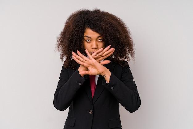 Jonge afro-amerikaanse zakenvrouw draagt een pak geïsoleerd op een witte achtergrond die een ontkenningsgebaar doet