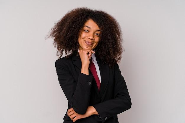 Jonge afro-amerikaanse zakenvrouw draagt een pak geïsoleerd op een witte achtergrond glimlachend gelukkig en zelfverzekerd, kin met de hand aanraken.