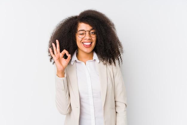 Jonge afro-amerikaanse zakenvrouw knipoogt een oog en houdt een goed gebaar met de hand.