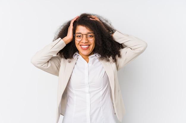 Jonge afro-amerikaanse zakenvrouw lacht vreugdevol handen op het hoofd te houden. geluk concept.