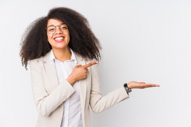 Jonge afro-amerikaanse zakenvrouw opgewonden met een kopie ruimte op palm.