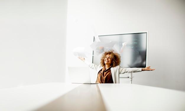Jonge afro-amerikaanse zakenvrouw papier in de lucht gooien na ontvangst van goed nieuws in het moderne kantoor