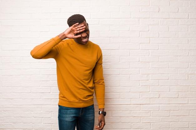 Jonge afro-amerikaanse zwarte man die gestrest, moe en gefrustreerd kijkt, het zweet van het voorhoofd droogt, zich hopeloos en uitgeput voelt op bakstenen muur
