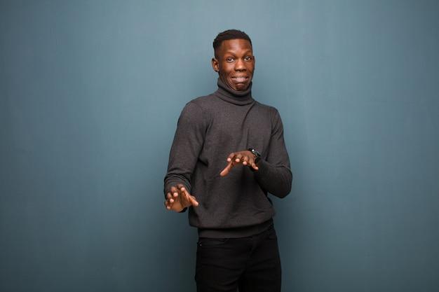 Jonge afro-amerikaanse zwarte man die walgt en misselijk voelt, zich terugtrekt van iets smerigs, stinkende of stinkende, zegt bah op grungemuur