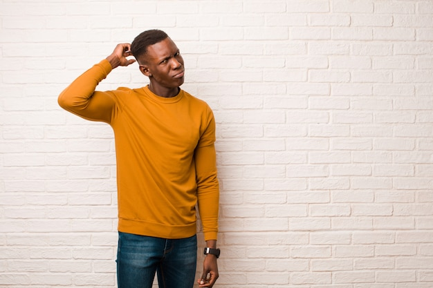 Jonge afro-amerikaanse zwarte man die zich verbaasd en verward voelt, hoofd krabt en naar de zijkant kijkt op bakstenen muur