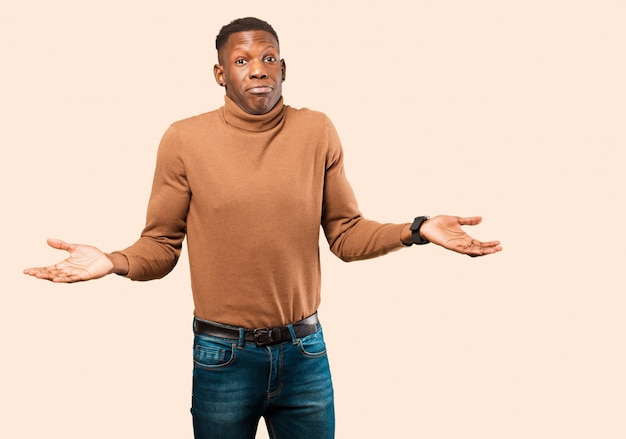 Jonge afro-amerikaanse zwarte man die zich verbaasd en verward voelt, twijfelt, weegt of verschillende opties kiest met grappige uitdrukking op beige muur