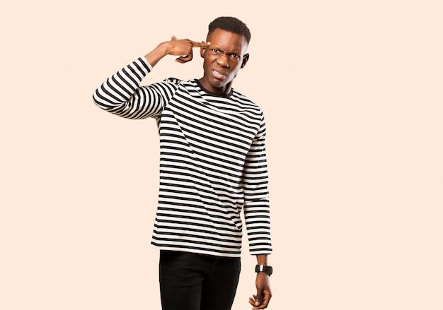 Jonge afro-amerikaanse zwarte man die zich verward en verbaasd voelt, laat zien dat je gek, gek of gek bent tegen een beige muur