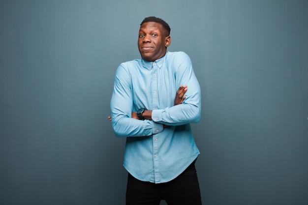 Jonge afro-amerikaanse zwarte man die zijn schouders ophaalt, zich verward en onzeker voelt, twijfelt met gekruiste armen en een verwarde blik