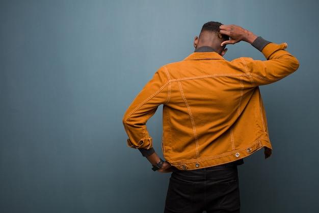 Jonge afro-amerikaanse zwarte man gevoel geen idee en verward, denken een oplossing, met hand op heup en andere op hoofd, achteraanzicht tegen grunge muur