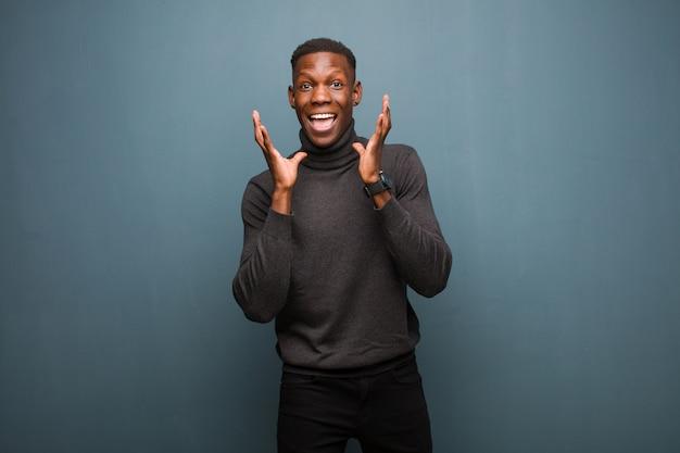 Jonge afro-amerikaanse zwarte man gevoel geschokt en opgewonden, lachend, verbaasd en gelukkig vanwege een onverwachte verrassing tegen grunge muur